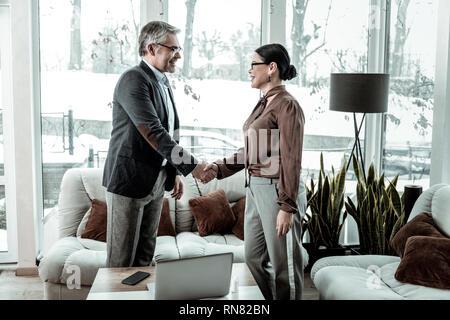 Dark-haired femme élégante dans un pantalon gris rencontre son associé Banque D'Images