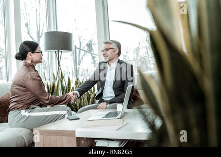 Bel homme aux cheveux gris et des lunettes à la tenue d'une réunion avec un nouveau partenaire d'affaires Banque D'Images