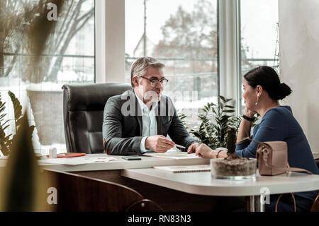 Homme sérieux aux cheveux gris lunettes en parlant de questions d'affaires avec son collègue Banque D'Images