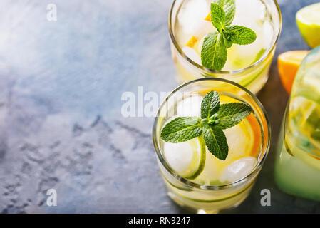 L'eau avec un citron et un tilleul en verres transparents sur une table avec l'espace de copie