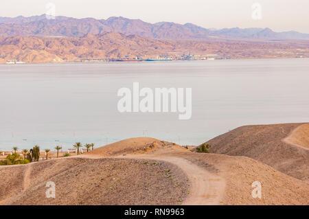 Courbe de sable autour de la voie des montagnes du désert jusqu'à la mer Rouge bay shore et les plages d'Eilat, Israël avec la Jordanie l'autre sur l'arrière-plan Banque D'Images