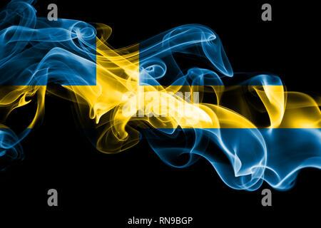 Drapeau national de la Suède fait de la fumée de couleur isolé sur fond noir. Résumé Contexte vague soyeuse Banque D'Images