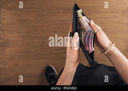 Vue de dessus de woman holding wallet avec billets hryvnia sur fond de bois
