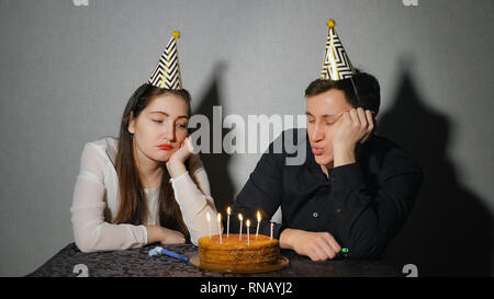 Sad lonely woman and man in party hat relaxing seul Banque D'Images