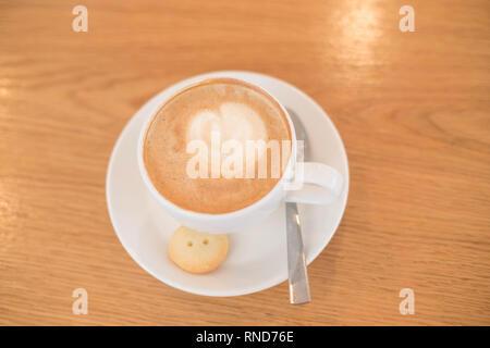 Tasse de café pour aller sur la table en bois avec latte art. Street Café. white tasse de Cappuccino. Trendy tonifiant. Composition minimale, hipster vibes. Haut Banque D'Images