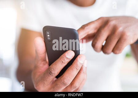 Close up of african american man hands using smartphone Banque D'Images
