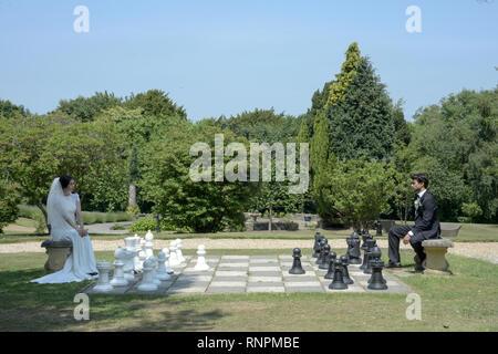 Un jeune couple pensif ont un mariage blanc traditionnel anglais, ils sont à la fois dark haired et bonne recherche mais semblent mécontents Banque D'Images