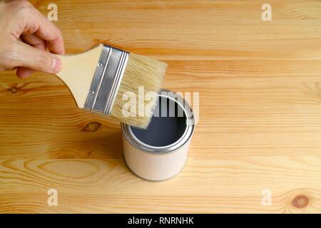 Hand holding Paintbrush atteindre la peinture ouvert isolé sur planche en bois avec de l'espace libre pour la conception ou le texte Banque D'Images