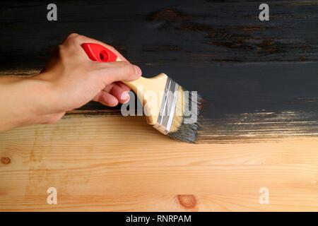 La main de l'homme tenant la planche en bois de peinture au pinceau avec de la peinture gris foncé Banque D'Images