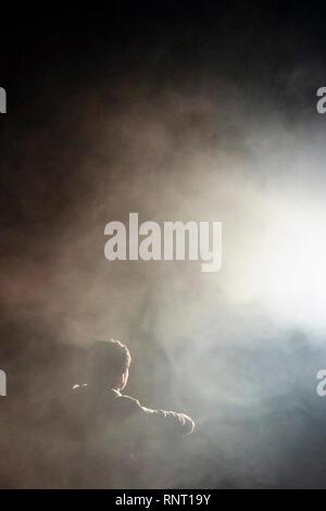 Jeune qui regarde une mystérieuse lumière vive illuminant des nuages de fumée ou de brouillard dans l'obscurité, convient pour une couverture de livre Banque D'Images
