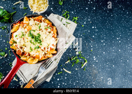 Casserole de Pâtes crémeuses au four, macaroni au fromage avec de la viande hachée, sol italien boeuf bolognaise en cocotte, bleu foncé fond béton copy space Banque D'Images
