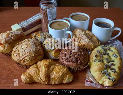 Muffins aux raisins secs et noix, gâteaux, roll et caps de café sur une table en bois brun. Close up. Focus sélectif. Banque D'Images