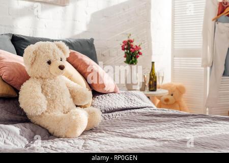 Portrait de l'ours en peluche jouet sur lit dans chambre à coucher moderne with copy space