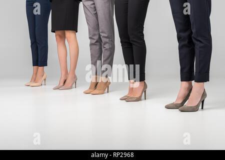 Portrait de la femme debout dans hight chaussures de talon sur fond gris Banque D'Images