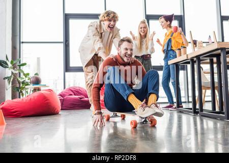 Smiling casual business colleagues having fun et équitation à roulettes dans bureau loft