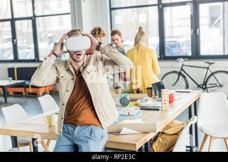 Designer hommes surpris avec des gestes tout en ayant les mains dans l'expérience de réalité virtuelle avec des collègues de bureau loft sur l'arrière-plan