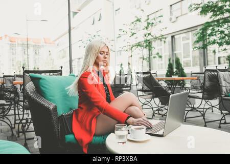 Travailler à l'extérieur. Pretty young business woman working on laptop in joli café en plein air, dame sur le déjeuner, le café, profitant de travail. - Image Banque D'Images