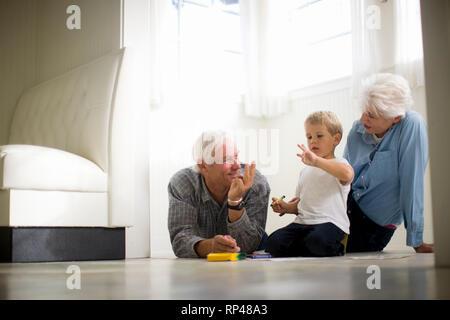 Jeune garçon assis sur le sol avec ses grands-parents. Banque D'Images