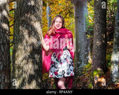 La nature teen girl countrygirl dans woodland forest entre les arbres portant écharpe rouge et jupe courte jupe mini happy laughing Banque D'Images