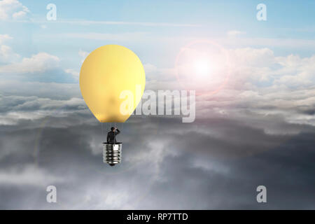 En homme d'ampoule jaune brillant hot air balloon flying over natural daylight sky background cloudscape Banque D'Images