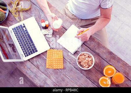 L'homme des notes sur les compléments alimentaires en mangeant des céréales pour petit-déjeuner Banque D'Images