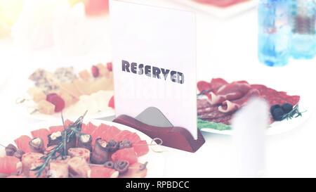 Un signe réservé sur la table de restaurant en plein soleil sur un fond de plats Banque D'Images