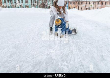 Jeune mère femme levait son garçon 2-3 ans glace en hiver dans la région de city park. Le concept de première leçon sur le patinage et support support, aide des parents dans Banque D'Images