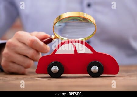 Close-up of a person's Hand Holding Magnifying Glass à la petite voiture rouge Banque D'Images