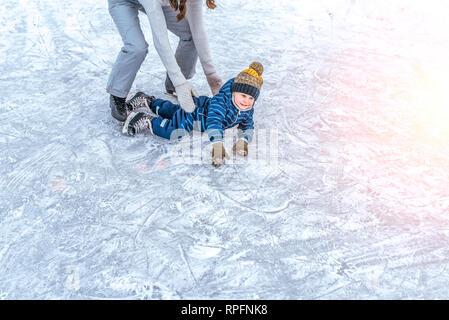 Jeune mère femme levait son garçon 4-6 ans glace en hiver dans la région de city park. Le concept de première leçon sur le patinage et support support, aide des parents dans Banque D'Images