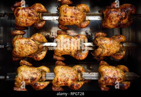 Des rangées de petites brochettes de poulet rôti cuit entier, ou du poulet rôti en Colombie, Amérique du Sud. Banque D'Images