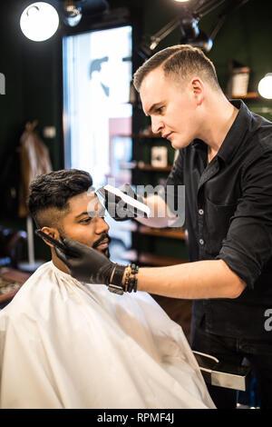 Des résultats professionnels. Close up portrait of young barbu se coupe par coiffure avec un rasoir électrique au salon de coiffure