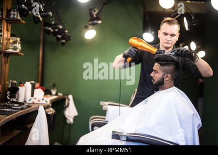 Close up portrait of young bearded man getting toiletté par coiffure avec sèche-cheveux au salon de coiffure Banque D'Images