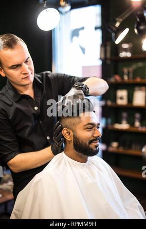 Les barbiers part propagation de la poudre de talc sur les clients professionnels avec cou blaireau en salon de coiffure pour hommes soin de beauté.concept.jeune homme noir ge