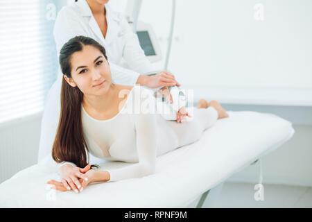 Portrait de femme brune vêtue de blanc body minceur LPG, looking at camera lors de l'obtention de massage intégral gpl, qui est effectuée par le l Banque D'Images