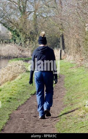 Middle aged Woman Walking le long d'un canal de halage en hiver portant un Bobble Hat Banque D'Images