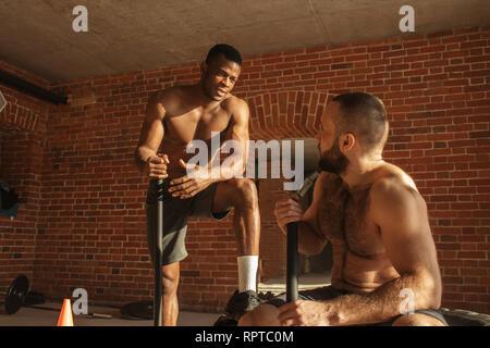 Deux mixed race bodybuilders parler durant une courte pause dans l'entraînement, les gars sont de frapper avec un marteau de pneu dans les murs de brique crossfit gym avec et p Banque D'Images