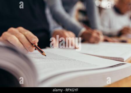 Close up de main de l'homme tenant un crayon et pointant vers le texte dans un livre. Cropped shot d'une personne lisant un livre tenant un crayon assis dans une cla