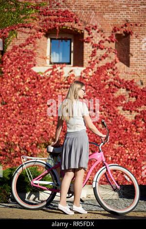 Vue arrière de très jolie femme blonde aux cheveux long dans des vêtements décontractés et des verres présentant à dame rose vélo sur bright chaude journée ensoleillée sur fond de mur couvert de belles feuilles de lierre rouge. Banque D'Images