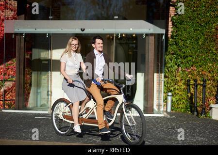 Young smiling couple, beau barbu et attractive blonde cheveux long femme vélo tandem sur journée ensoleillée par ouvrir la porte de verre de bâtiment en brique rouge entièrement recouverts de feuilles de lierre. Banque D'Images