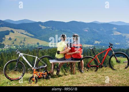 Vue arrière de touristes de la famille des motards, mère, père et enfant assis sur le banc en bois, enlacés, se reposant après cycling mountain bikes on grassy hill dans les montagnes. Concept relations heureux Banque D'Images