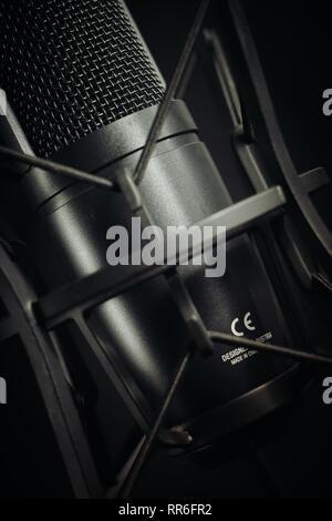 Microphone de studio à angle pour le centre de l'image sur un fond sombre, l'aspect vertical. Banque D'Images