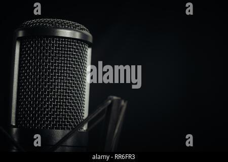Microphone de studio à gauche de l'image sur un fond sombre, aspect horizontal. Banque D'Images