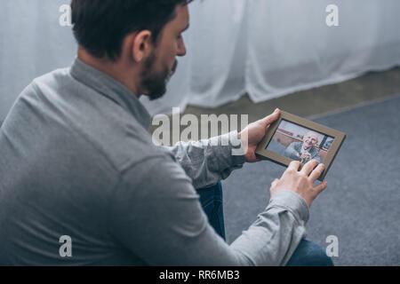Portrait de l'homme assis et regardant la photo dans le châssis avec homme mûr à la maison, concept trouble en deuil Banque D'Images