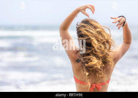 Cute girl portrait avec de longs cheveux bruns bouclés et un tatouage sur l'omoplate pendant que la femme est à la recherche à l'horizon à une plage sauvage