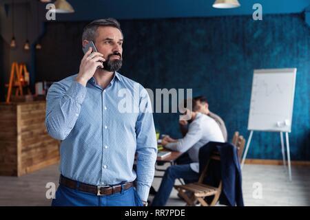 Handsome man parle sur le téléphone mobile tout en travaillant dans le bureau.