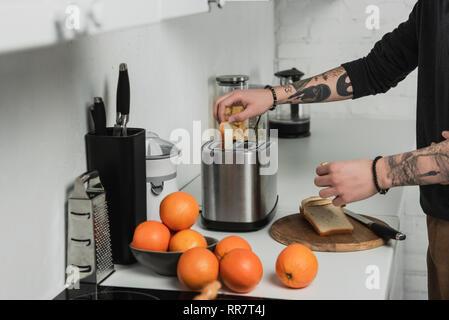 Portrait de l'homme tatoué la préparation des toasts avec grille-pain pendant le petit-déjeuner dans la cuisine Banque D'Images