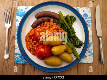 Un Yorkshire repas de saucisses, haricots, tomates grillées, pommes de terre nouvelles et tenderstem le brocoli sur une plaque légèrement bleu sur une table en bois Banque D'Images