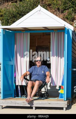 Bournemouth, Dorset, UK. Feb 25, 2019. Météo France: une autre belle chaude journée ensoleillée à Bournemouth comme visiteurs profiter du soleil à la plage sur la journée la plus chaude de l'année et les plus chaudes jamais jour de février. L'homme se détendre au soleil à Beach Hut. Credit: Carolyn Jenkins/Alamy Live News Banque D'Images