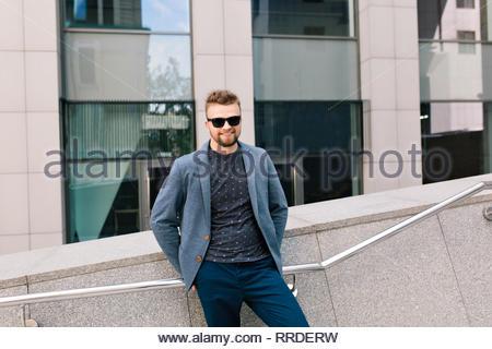 Portrait de l'Homme à lunettes sur office building arrière-plan. Il porte un T-shirt, veste, jeans, barbe. Il sourit à la caméra. Banque D'Images