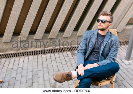 Beau mec est assis sur une chaise en plein air, sur fond de mur de béton. Il porte manteau gris, jeans, lunettes de soleil. Banque D'Images